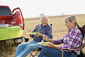 Senior couple enjoying lunch in crop field - Stock Image - E89GWA
