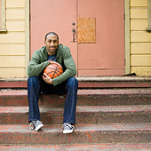 African American man sitting on steps with basketball - Stock Image - BKMA62