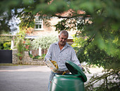 Man composting food scraps - Stock Image - CYKXPR