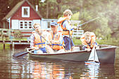 Brothers, father and grandfather fishing from canoe on lake - Stock Image - ECXG8P