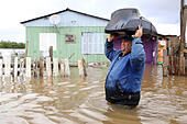 Gravatai, Brazil. 21st July, 2015. A man carries his TV set as he wades through floodwater in the area of Vila Rica in Gravatai town, state of Rio Grande do Sul, Brazil, on July 21, 2015. More than 50,000 people are affected by the strong floods in the Brazilian state of Rio Grande do Sul, the regional Civil Defense said on Tuesday. © Pedro H. Tesch/ELEVEN/AGENCIA ESTADO/Xinhua/Alamy Live News - Stock Image - EY4W58