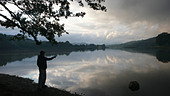 Man looking out over still lake - Stock Image - CTYXXR