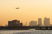 Regional airliner landing at London City Airport with Canary Wharf Docklands in the background, UK - Stock Image - B8F1M2