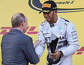Sochi, Russia. 12th Oct, 2014. Russia's president Vladimir Putin (L) and Mercedes' Lewis Hamilton of the UK (1st place) shake hands during the awards ceremony for the 2014 Formula One Russian Grand Prix at the Sochi Autodrom racing circuit. © Sergei Savos - Stock Image - E8NR7M