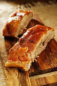 Roast belly pork on chopping board - Stock Image - BJPN15