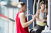 Two people using weight machines in fitness center - Stock Image - DA71FX