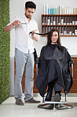 A woman having her hair cut by a male hairdresser - Stock Image - C44B54