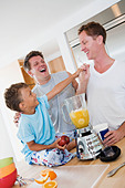 Gay couple making smoothies with their son - Stock Image - AHNBMG
