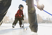Father and son playing ice hockey on rink - Stock Image - DXPF3K