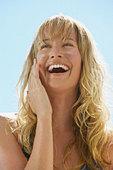 Closeup of woman applying sunblock to cheeks laughing - Stock Image - AA6B0N