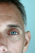 Closeup Portrait of a Baby Boomer Man with Piercing Blue Eyes Using Selective Focus He is Looking into Camera Lens Copy Space - Stock Image - B4BCB1