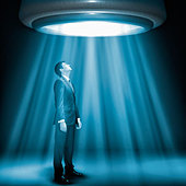 Caucasian businessman standing underneath glowing lights - Stock Image - CWJ6MF