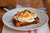 Classic Swedish open faced sandwich of sliced boiled egg topped with Kalle's kaviar and sprinkled with chopped chives. - Stock Image - CB5YDF