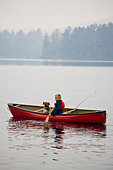 Young boy going fishing with dog in canoe on Source Lake, Algonquin Provincial Park, Ontario, Canada. - Stock Image - CFAM0M