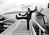 Richard Branson drinking from a bottle of champagne as he celebrates Virgin Atlantic Airlines inaugural flight June 1984 - Stock Image - B4GAG4