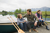 Family sitting by canoe by still lake - Stock Image - E6RD34