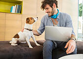 Man petting dog in office - Stock Image - E59HMY