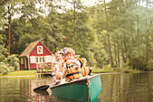 Father and sons fishing from canoe in lake - Stock Image - ECXG4G