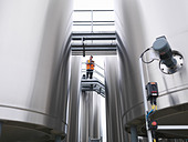 Worker checking tanks in bottling plant - Stock Image - C7PFE3