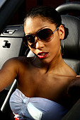 YOUNG WOMAN IN HER CAR WEARING SUNGLASSES MOODY LIGHTING - Stock Image - ATAC8X