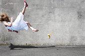 Girl slipping on a banana - Stock Image - BBTKRJ