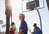 Older men playing basketball on court - Stock Image - D2XGGT