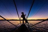 Silhouette of fisherman rowing canoe on water - Stock Image - D6EC1R
