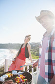 Man and woman tending barbecue with ocean in background - Stock Image - BK4XB3