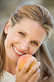 A woman holding a peach - Stock Image - A7H1TX