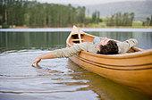 Man reclining in canoe on lake - Stock Image - BCA194