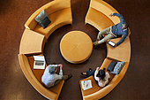 Overhead view of business people talking on circular sofa - Stock Image - EHMF62