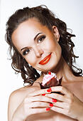 Gourmet. Happy Young Woman holding Cupcake with Whipped Cream - Stock Image - E1HM0W