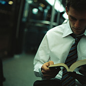 Man reading in subway car - Stock Image - BCKW90