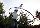 Low angle view of a girl playing with a hula hoop - Stock Image - D71CGK