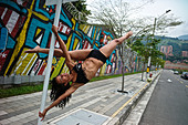 A dancer performs a pose on a pole outdoors next to a urban grafitti. - Stock Image - CY1JYM