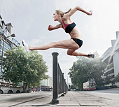 Athlete jumping over banister on street - Stock Image - C84C33