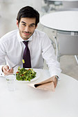 A man reading a newspaper whilst having his lunch - Stock Image - B7MN61