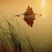 Couple on a row boat during the sunset - Stock Image - BKNAT8
