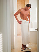 Man wrapped in a towel standing on bathroom scale with hands on hips - Stock Image - BK5005