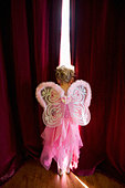 Girl (4-6) with fairy wings looking out gap in curtains, rear view - Stock Image - BA62N5