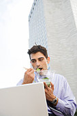 A businessman using a laptop and eating his lunch - Stock Image - A7GM9P