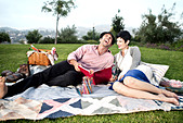 Barefoot, stylish couple relaxing and picnicking on a lush green lawn of a park. The man is laughing and sketching in a book. - Stock Image - C45HYA