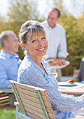 Portrait of smiling senior woman enjoying lunch at table in sunny garden - Stock Image - CC9D4X