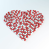 Red and white capsules forming a heart shap - Stock Image - D0RK5P