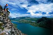 Hiker sitting above Gjende (or Gjendin) Lake in the Jotunheimen mountains in Norway's Jotunheimen National Park - Stock Image - BEFKCE