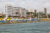 Larnaca Finikoudes Beach with hotels and sunbathers, - Stock Image - E1JFWG
