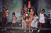 Street scene at night with children an old man and a baby in Central Havana Cuba - Stock Image - AFXB2J