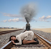 Mixed race businesswoman kneeling on railroad tracks - Stock Image - CR5A7P