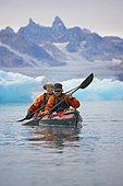Men rowing canoe on still glacial sea - Stock Image - CR21NE