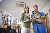 Veterinarian holding dog in lobby - Stock Image - D14KKA